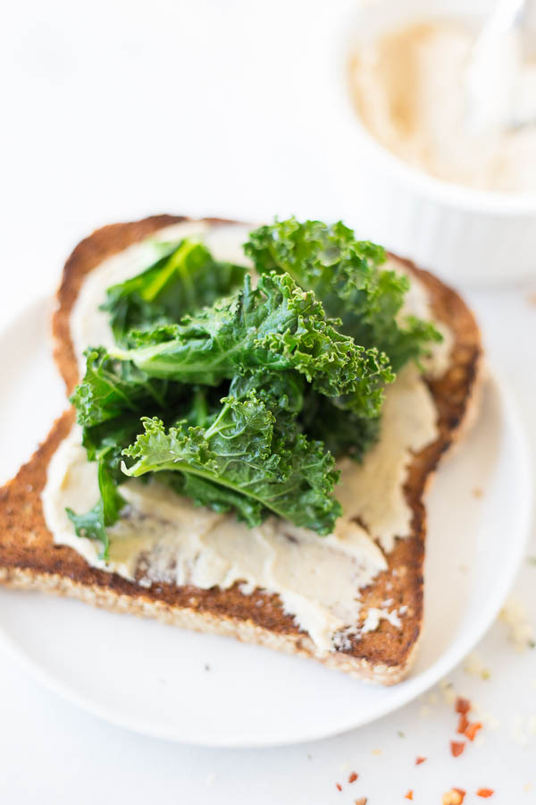Hummus Kale Toast: a delicious gluten free and vegan breakfast or snack! Flavors like garlic, lemon, and red pepper flakes make for a truly spectacular toast!    fooduzzi.com recipes