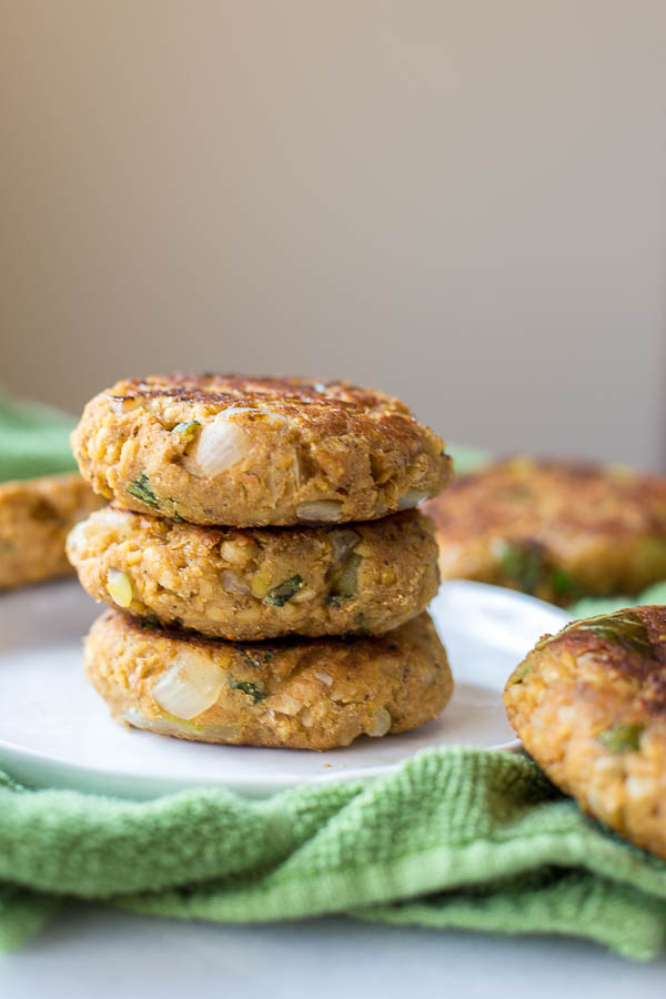 Italian-Style Chickpea Burgers: packed with healthy, vegan, and gluten free ingredients and topped with caramelized onion, hummus, and basil! Perfect for Father's Day and summer cookouts! || fooduzzi.com recipe