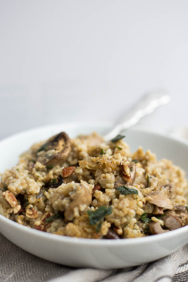 Steel Cut Oat Stuffing with Mushrooms & Fried Sage: A warm and comforting Thanksgiving staple! This gluten free & vegan stuffing is loaded with garlicky mushrooms, fried sage, and crispy pecans! || fooduzzi.com recipe
